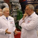 Igor Arbuzov et Dmitry Rogozine en discussion devant un stand de montage.
