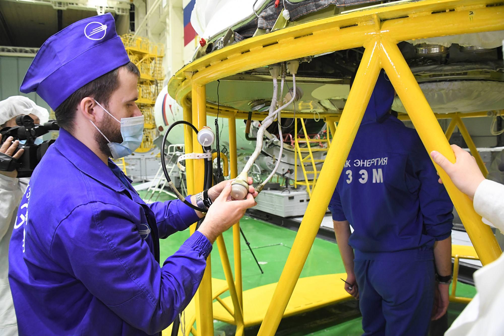 """Soyouz MS-18 est provisoirement posé sur un portique facilitant le travail """"sous"""" ou """"à l'arrière"""" du véhicule."""