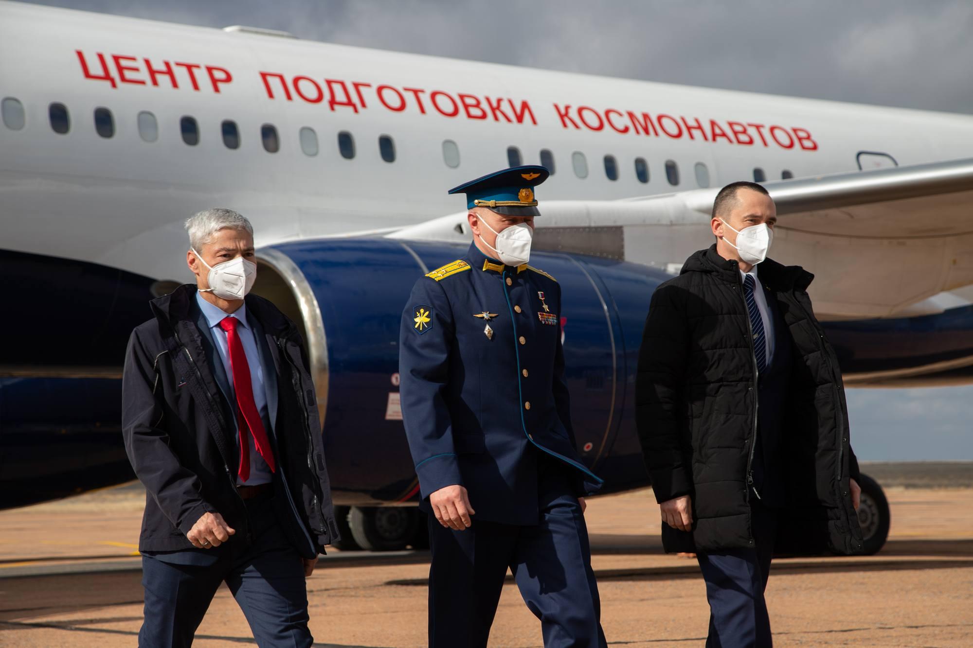L'équipage principal de Soyouz MS-18 descend d'avion pour être accueilli par les responsables du vol.