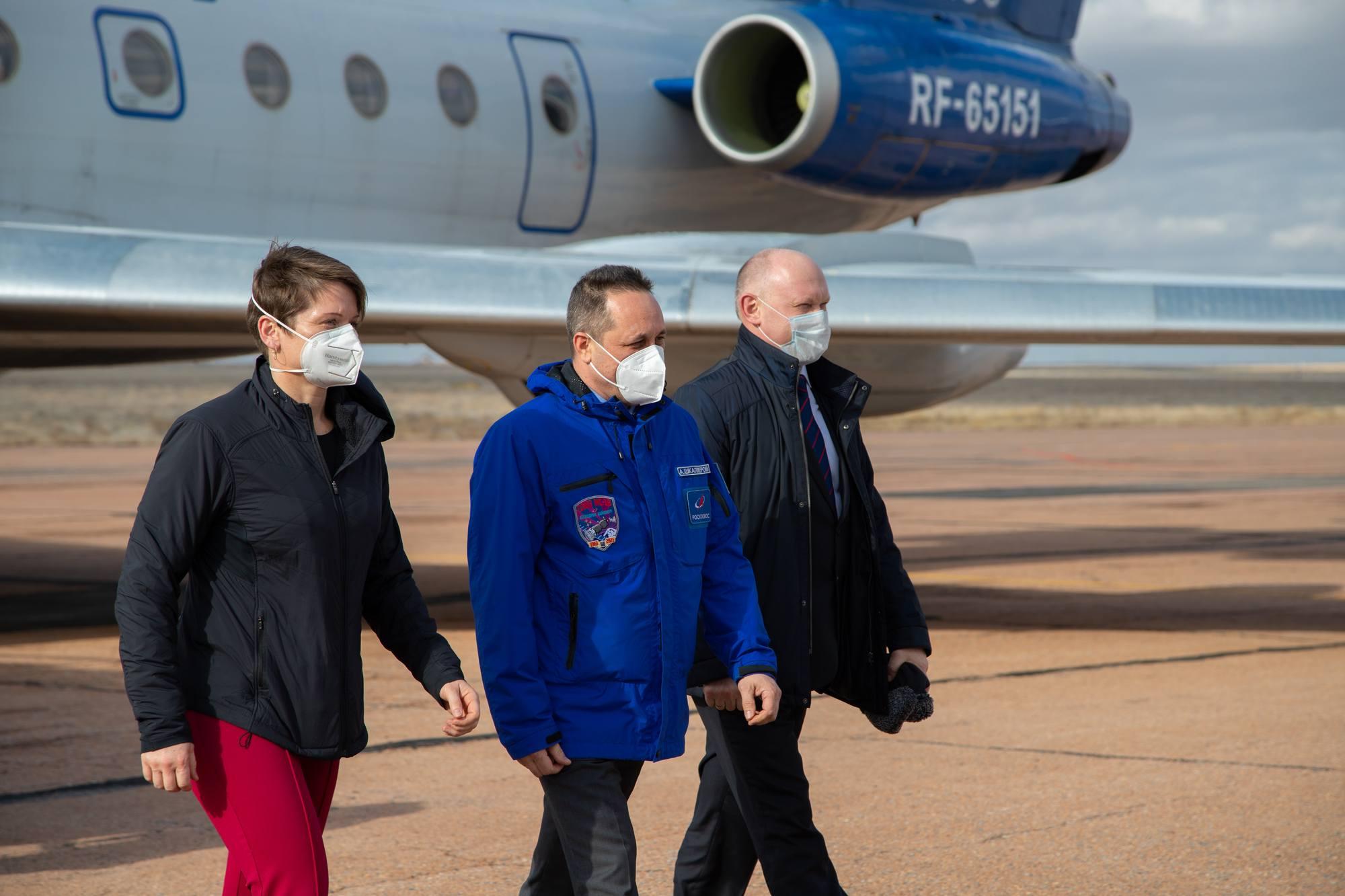 L'équipage descend d'avion pour être accueilli par le même comité d'accueil.