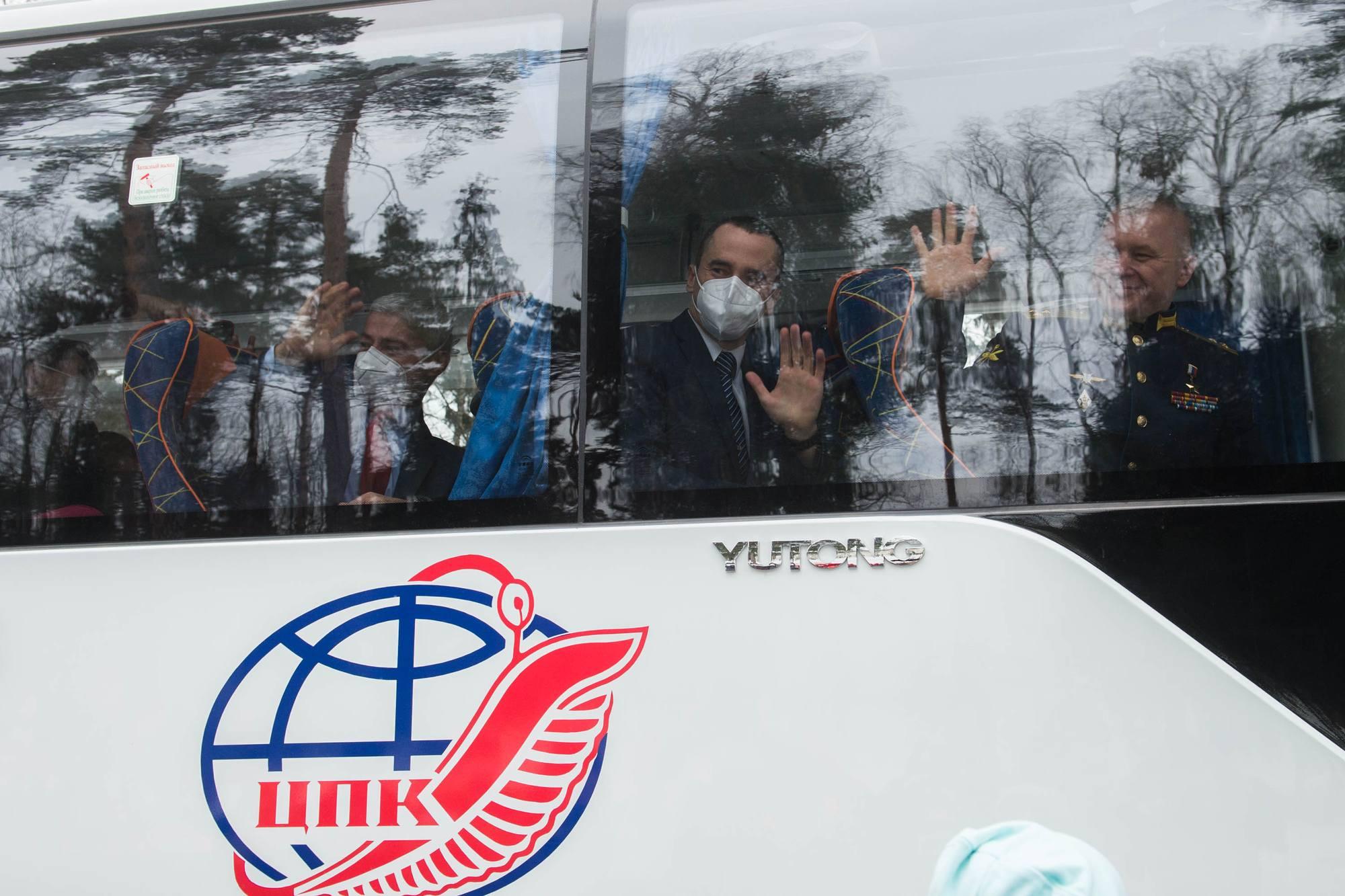 L'équipage principale salue les proches à travers les vitres du bus du TsPK.