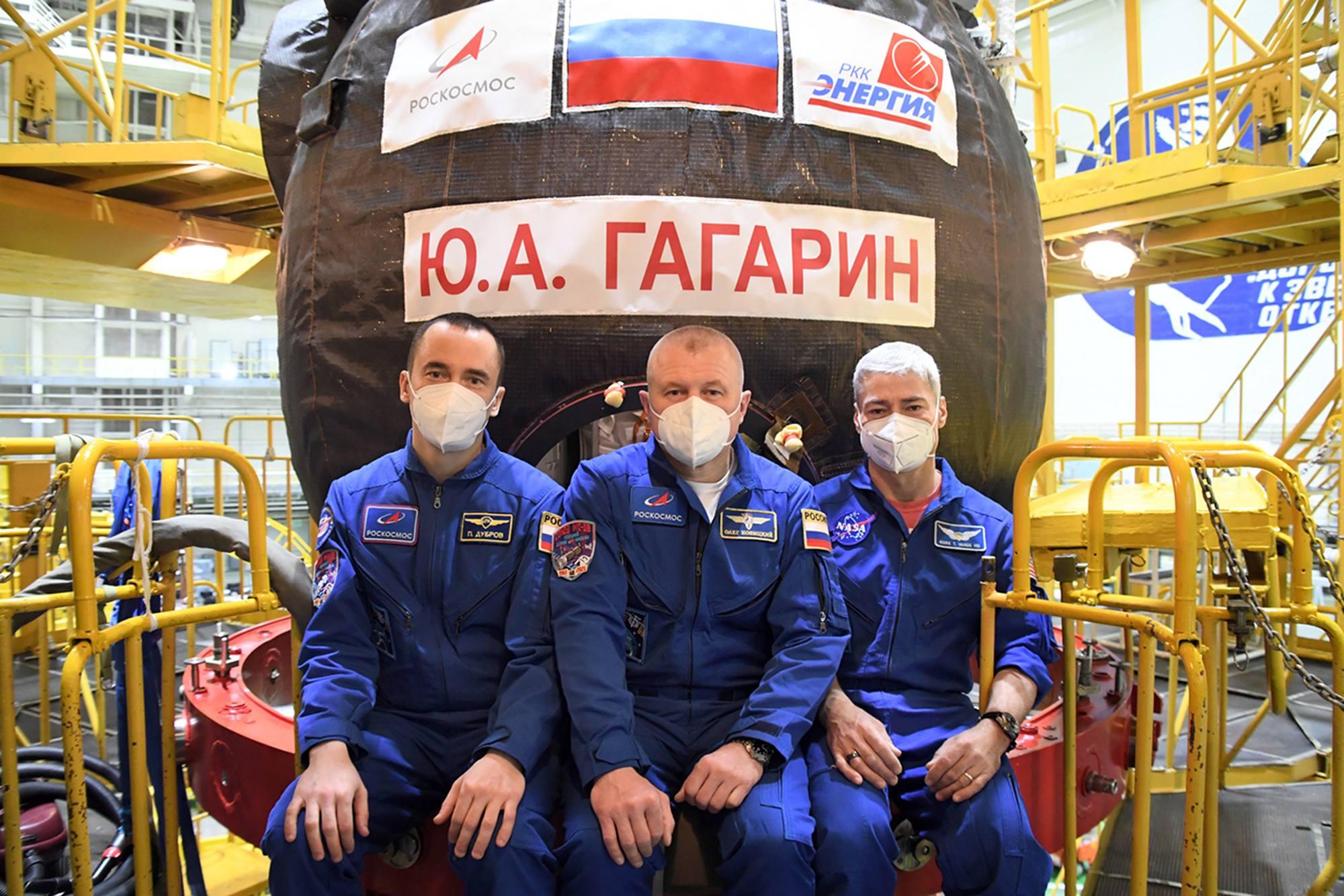 L'équipage principal de vant le compartiment orbital de Soyouz MS-18 arborant le nom de Youri Gagarine.