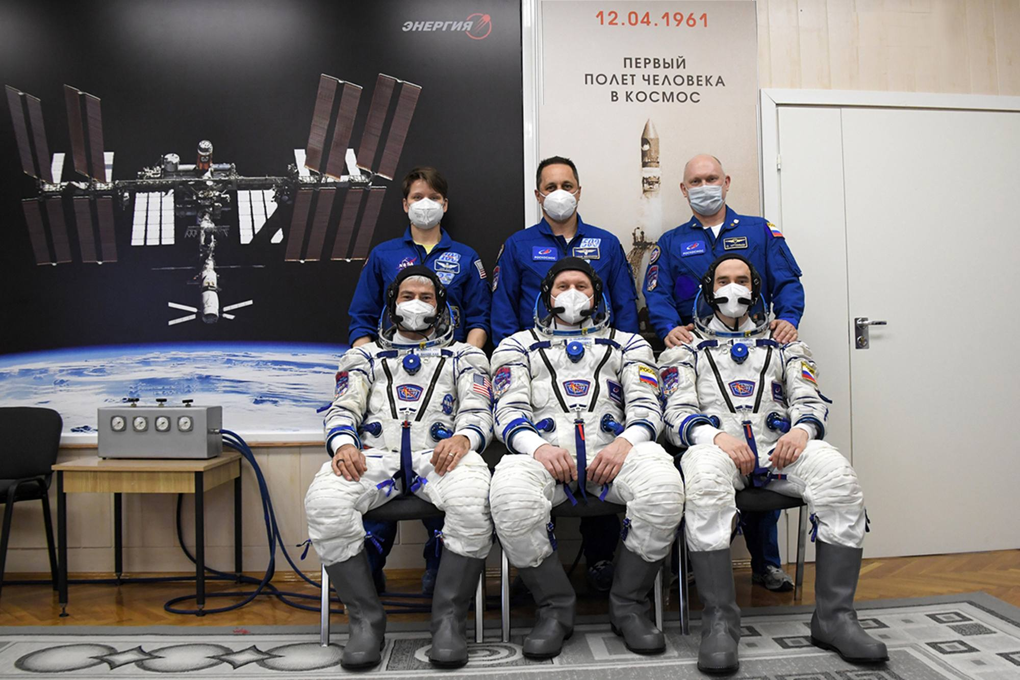 Les deux équipages posant devant l'affiche du lancement du premier cosmonaute de l'histoire de l'humanité.