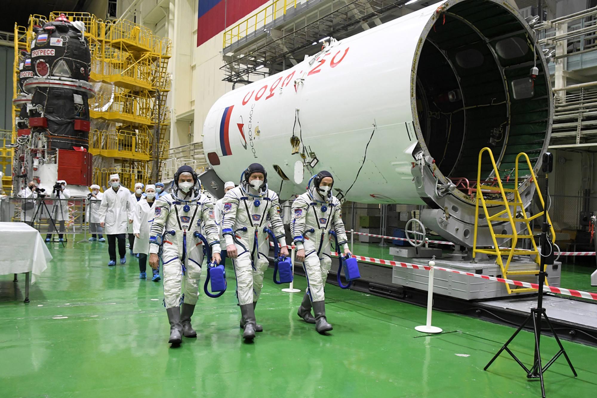 Les cosmonautes gagnent le stand où est situé Soyouz MS-18 et passent devant la coiffe.