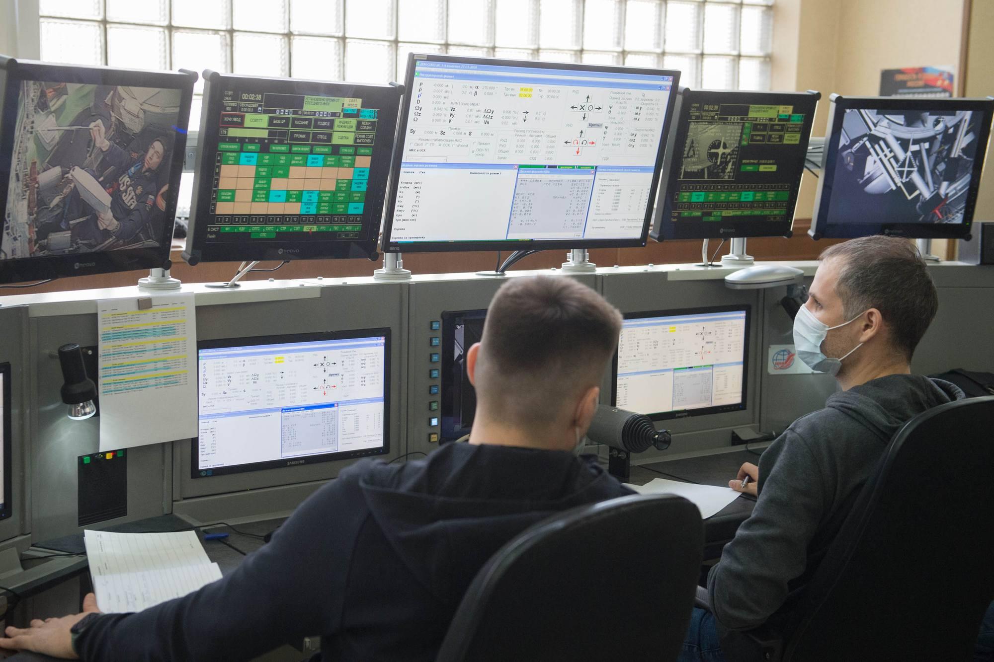 Les contrôleurs surveillent l'activité du cosmonaute sur le simulateur de rendez-vous manuel.