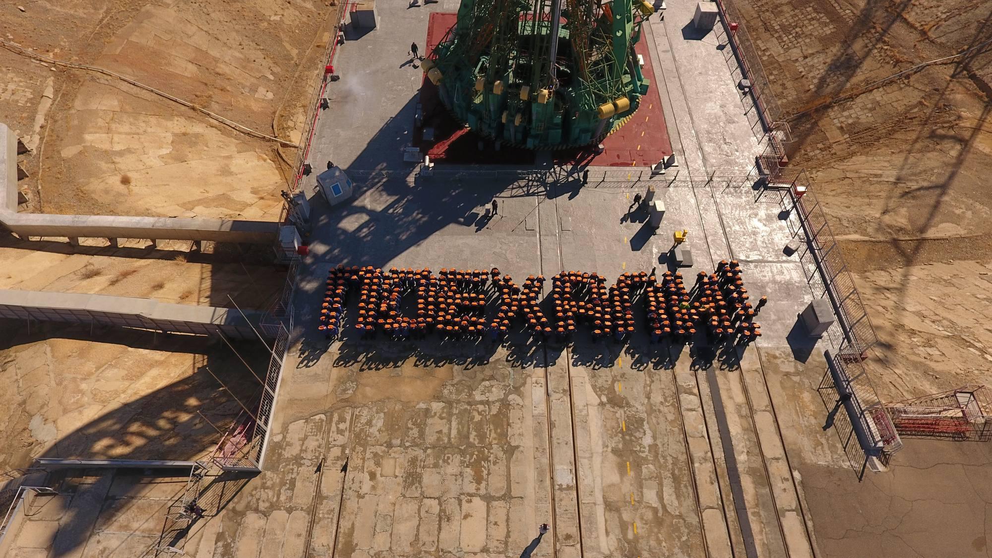 Les employés formant le mot Poekhali! au pied de la tour de service du pas de lancement n°1 de Baïkonour.