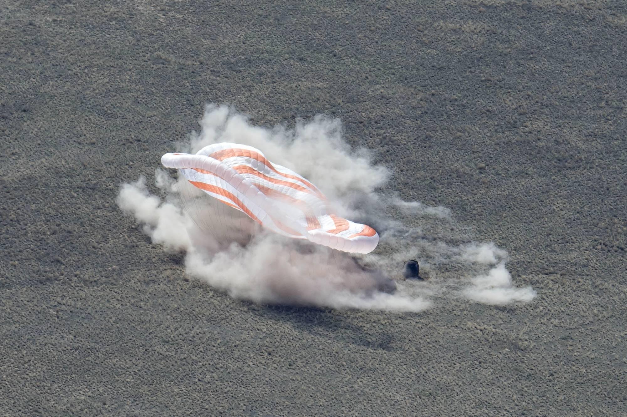 Le parachute se dégonfle dans la fumée et la poussière provoquées par les rétro-fusées de la capsule qui s'est posée debout.
