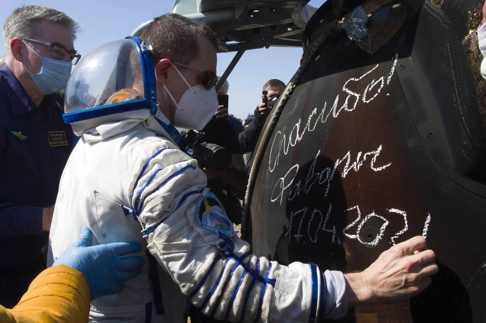 """Sergueï Ryzhikov inscrivant sur la capsule d eretour: """"Merci, Favorit""""."""