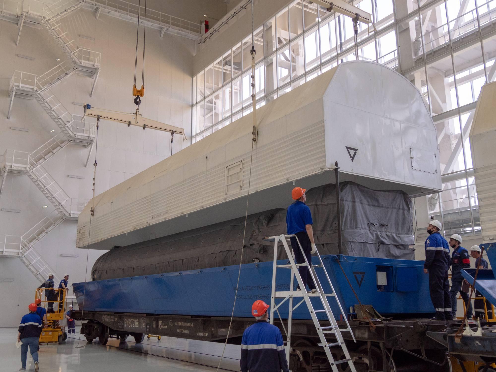 On soulève le couvercle du wagon de transport. A la forme on reconnaît déjà la partie inférieure du corps central du lanceur Soyouz.