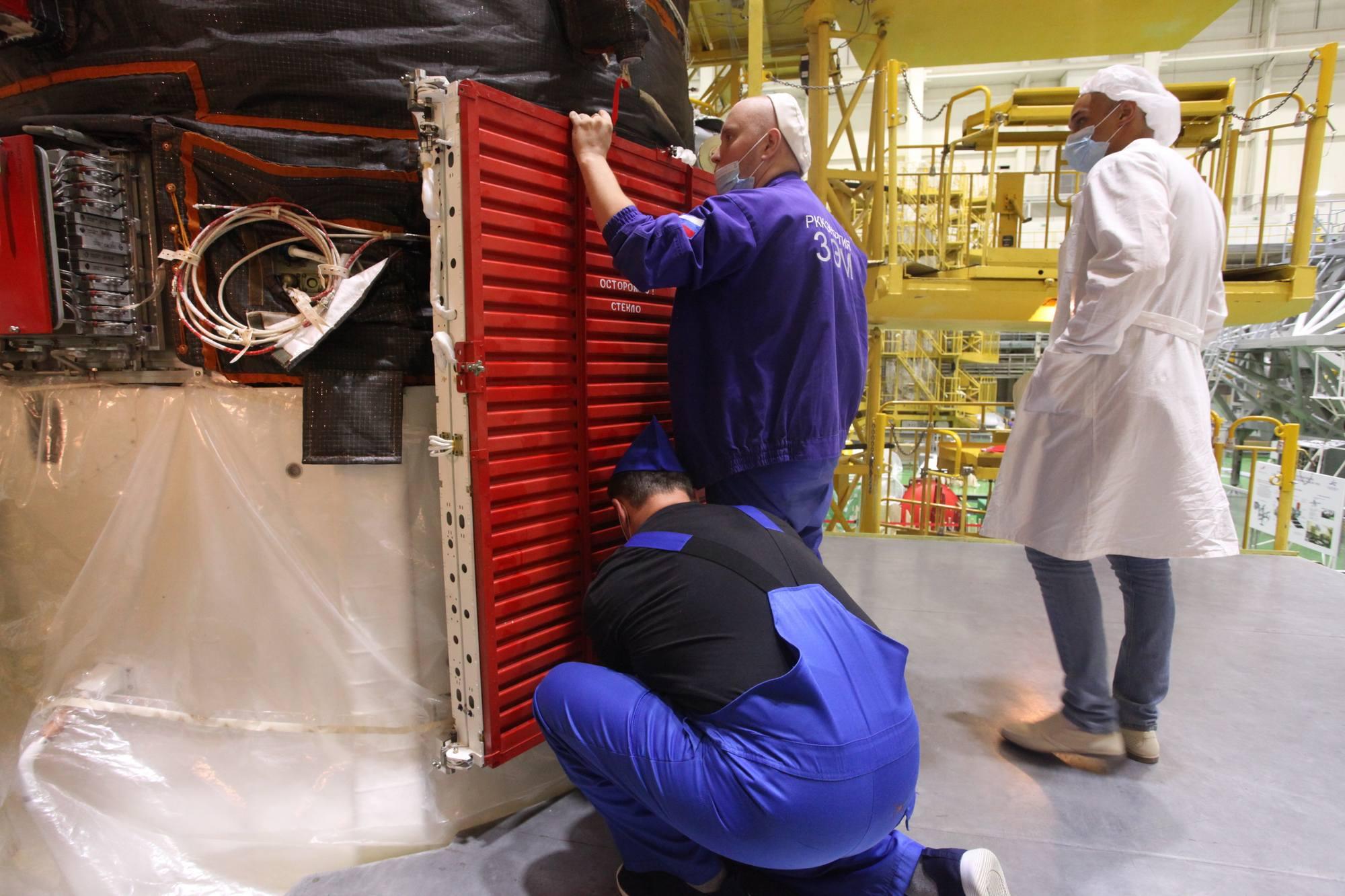 Image typique de la façon de travailler russe: Les techniciens (en bleu) effectuent les opérations sous le contrôle des ingénieurs (en blanc).