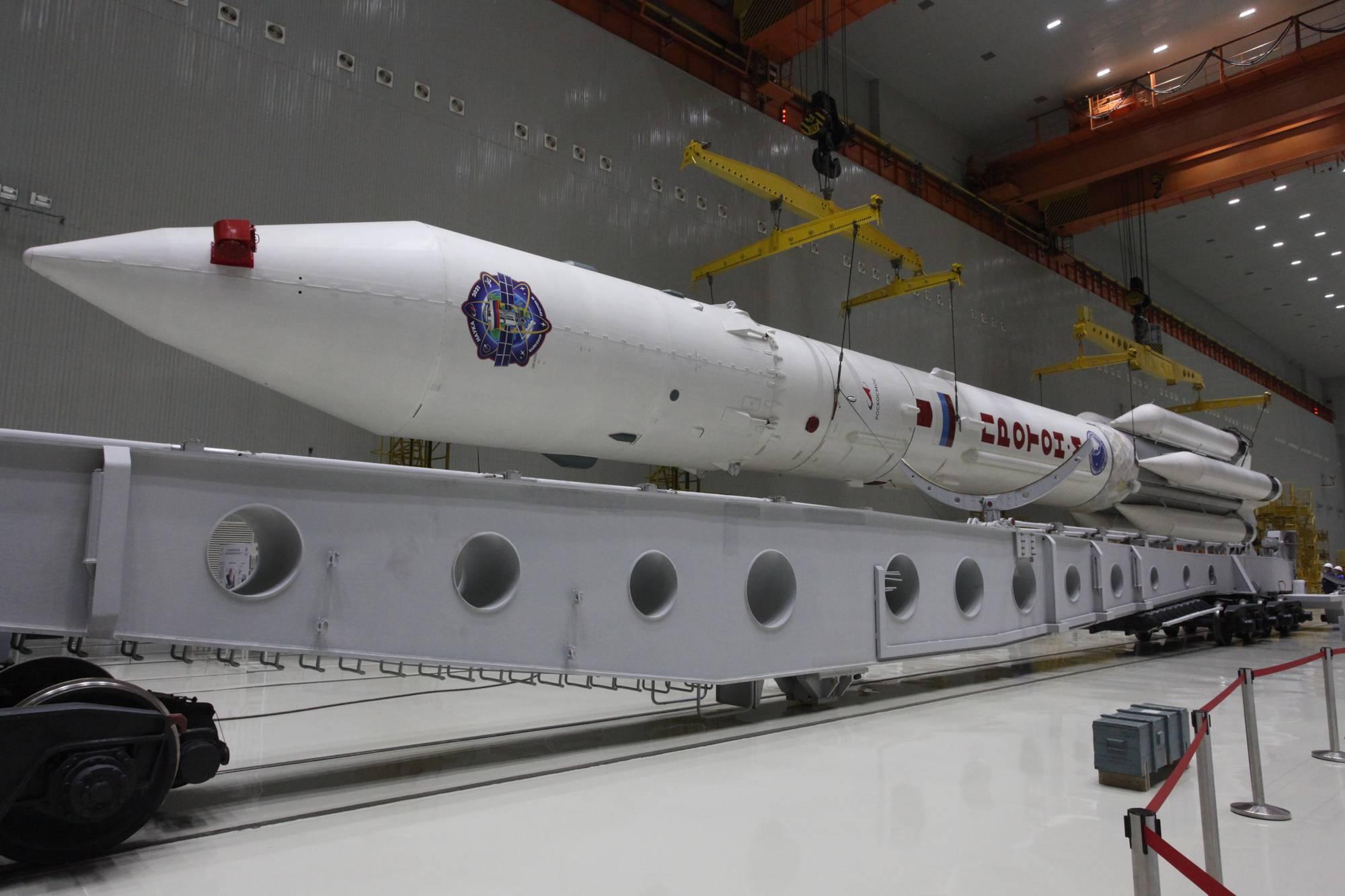 La fusée est soulevée par un pont roulant.