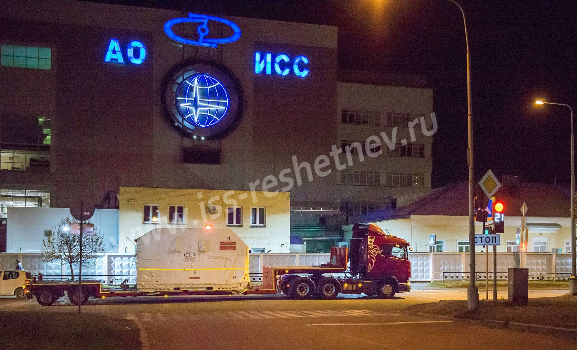 La façade de l'entraprise avec un camion emportant un satellite vers l'aéroport. Image d'archives.