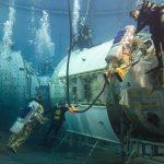 Les deux femmes travaillant sur les modèles des modules du segment russe de l'ISS, installés au fond du bassin.